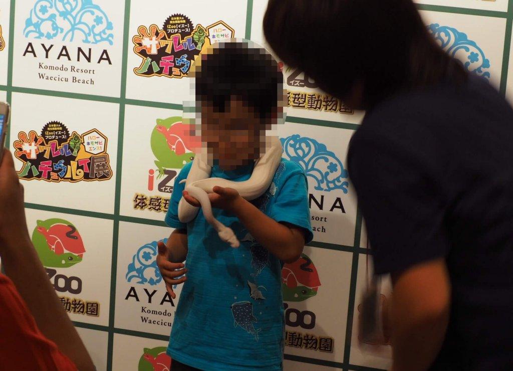 少年がヘビと記念撮影している様子